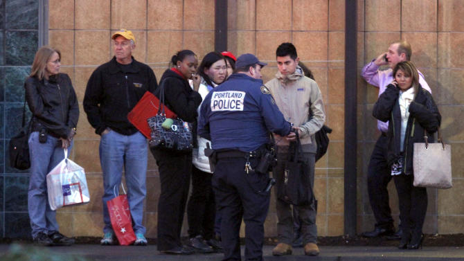 CORRECTS MALL LOCATION - A police officer conducts interviews with mall patrons outside the Clackamas Town Center in Portland, Ore. Tuesday, Dec. 11, 2012. A gunman is dead after opening fire in the Portland, Ore., area shopping mall Tuesday, killing two people and wounding another, sheriff's deputies said. (AP Photo/The Oregonian, Bruce Ely)  MAGS OUT; TV OUT; LOCAL TV OUT; LOCAL INTERNET OUT; THE MERCURY OUT; WILLAMETTE WEEK OUT; PAMPLIN MEDIA GROUP OUT