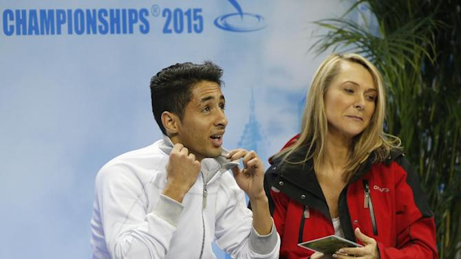Chafik Besseghier of France sits weigh his coach as the wait for his score in the Men Free Skating event in the ISU World Figure Skating Championship 2015 held at the Oriental Sports Center in Shanghai, China, Saturday, March 28, 2015. (AP Photo/Ng Han Guan)