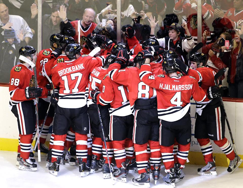 Chicago Blackhawks' Brent Seabrook (7) celebrates with teammates after scoring his game-winning goal during the overtime of an NHL hockey game against the Columbus Blue Jackets in Chicago, Friday, March 1, 2013. The Blackhawks won 4-3. (AP Photo/Nam Y. Huh)