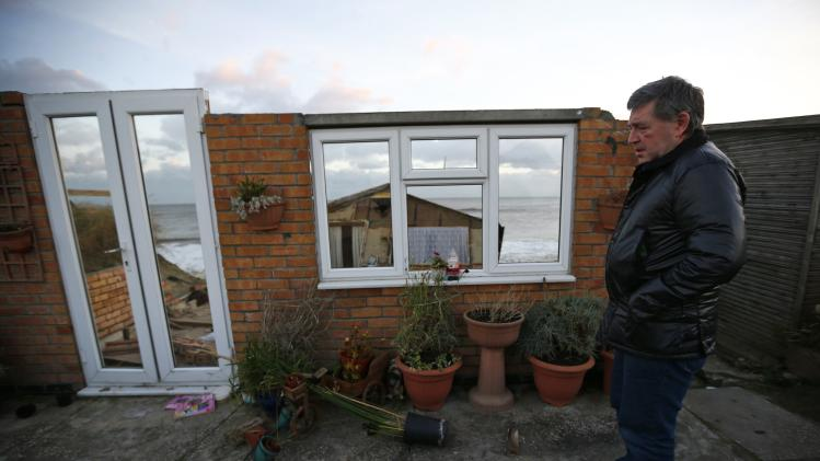 Steve Connelly looks at the remains of his home after it fell into the sea during a storm surge in Hemsby, eastern England