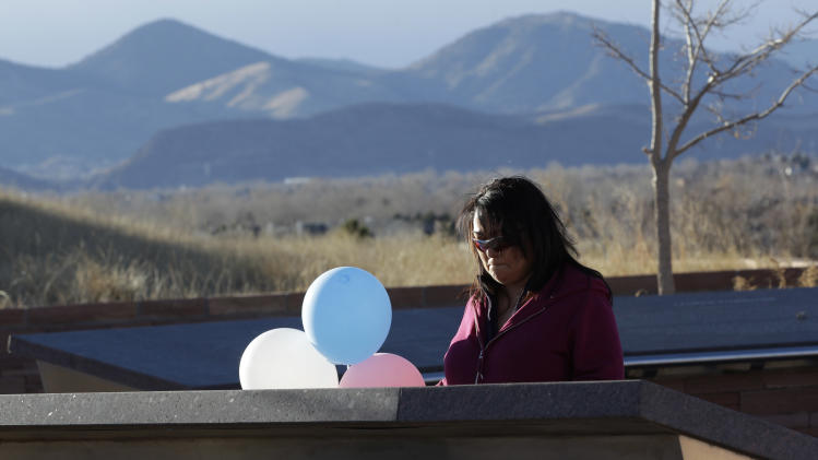 CORRECTS YEAR PHOTO WAS TAKEN - A former student at Columbine High School, who preferred her name not be used, reads a plaque at the Columbine Memorial, where someone had left balloons and a note for the victims of last week's deadly shootings at a Connecticut elementary school, in Littleton, Colo., Monday Dec. 17, 2012. Columbine and other sites of mass shootings have been rebuilt by residents determined to reclaim public places invaded by gunmen. Deciding what to do with the scene of a tragic event often determines how a community will heal. (AP Photo/Brennan Linsley)