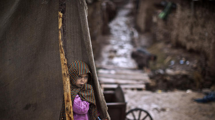 An Afghan refugee girl, looks at men trying to clear sewage paths so rainwater can drain on the outskirts of Islamabad, Pakistan, Tuesday, March 11, 2014. (AP Photo/Muhammed Muheisen)