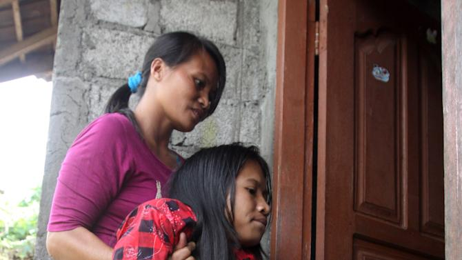 In this April 22, 2012 photo, Putu Restiti, is carried by her mother Jero Widiani into their house in Songan village, Kintamani, Bali, Indonesia. Restiti and her sister Alit Astini were kept out of school and had no friends. But like children everywhere, they had powerful imaginations. After being given a Barbie doll, they started stitching tiny, intricate outfits for her from their mother's sewing scraps. And in doing so, they created a new world for themselves. (AP Photo/Firdia Lisnawati)