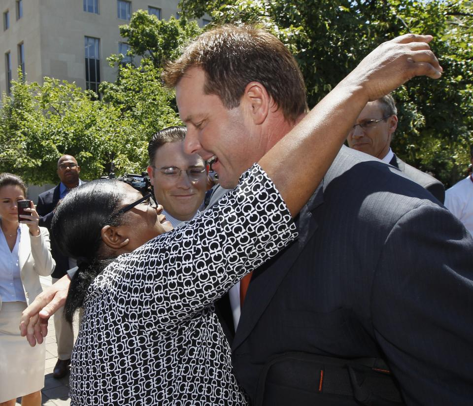 Former Major League baseball pitcher Roger Clemens gets a hug as he leaves federal court in Washington, Thursday, July 14, 2011, after the judge declared a mistrial in his perjury trial after prosecutors showed jurors evidence that the judge had ruled out of bounds.  (AP Photo/Alex Brandon)