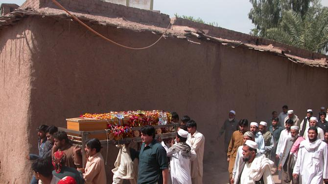 Pakistani villagers carry the body of a community police officer killed in an attack, for burial in suburbs of Peshawar, Pakistan on Tuesday, April 2, 2013. Several dozen militants armed with assault rifles and rocket-propelled grenades attacked a power grid station in northwestern Pakistan before dawn Tuesday, killing many people and taking hostages, police said. (AP Photo/Nasir Khan)