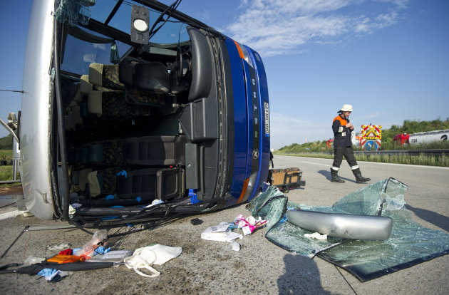 A firefighter walks past a bus overturned on the highway near Freising, southern Germany, Wednesday, Aug. 22, 2012. German police say at least 30 children have been injured, some of them seriously, after the bus they were traveling in overturned on the highway. A Bavarian police spokesman says the driver appeared to have lost control of the bus during a sudden hailstorm. (AP Photo/dapd, Lukas Barth)
