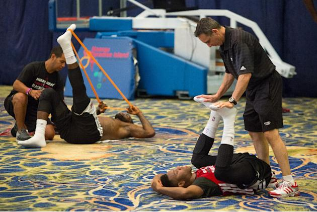 Miami Heat guard Norris Cole, right, and forward LeBron James stretch after training at the Atlantis resort on Paradise Island, Bahamas, Wednesday, Oct. 2, 2013. The two-time defending NBA champions a