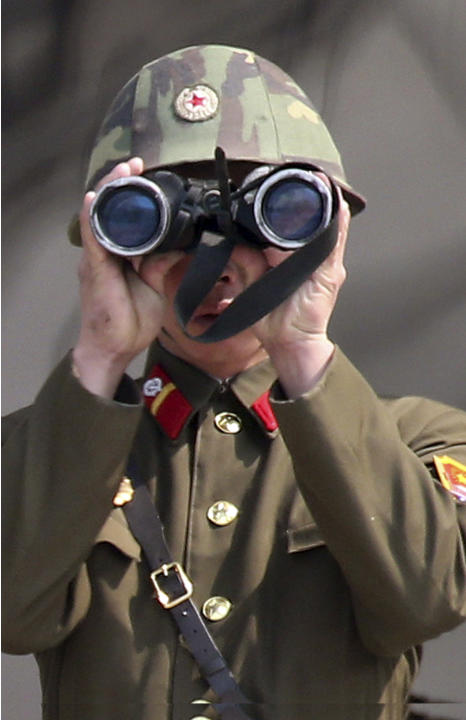 A North Korean soldier uses a pair of binoculars to watch the South Korean side at the border village of Panmunjom in the demilitarized zone (DMZ) in South Korea Thursday, April 4, 2013. South Korea's