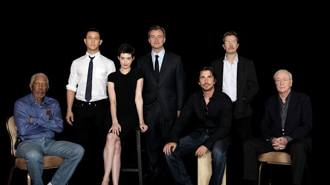 """In this July 7, 2012, photo, from left, actor Morgan Freeman, actor Joseph Gordon-Levitt, actress Anne Hathaway, director Christopher Nolan, actor Christian Bale, actor Gary Oldman, and actor Michael Caine, from the upcoming film """"The Dark Knight Rises,"""" pose during a photo shoot in Beverly Hills, Calif. """"The film will be released in theaters on July 20. (Photo by Matt Sayles/Invision/AP)"""