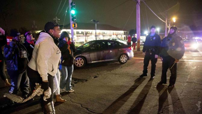 Protesters confront police in an intersection after a man was fatally shot by a policeman in Berkeley, Missouri