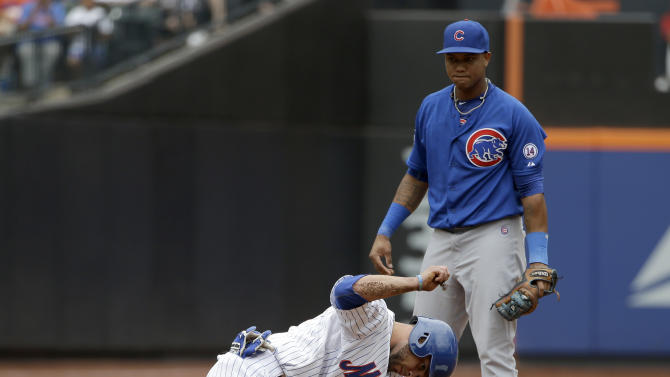 While Chicago Cubs shortstop Starlin Castro, top, looks on, New York Mets' Johnny Monell reacts after being called out at second base during the fifth inning of the baseball game at Citi Field, Thursday, July 2, 2015 in New York. (AP Photo/Seth Wenig)
