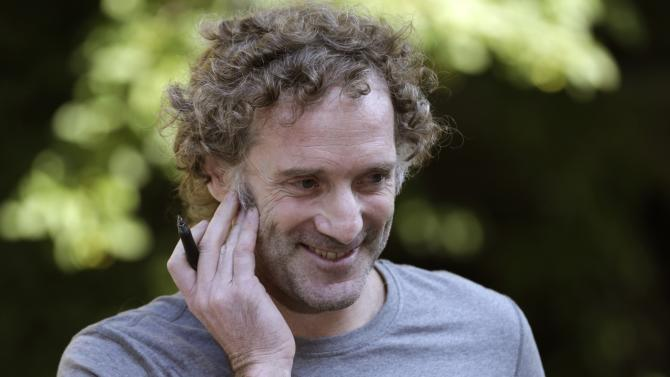 Peter Theo Curtis smiles as he talks with reporters outside his mother's home in Cambridge, Mass., Wednesday, Aug. 27, 2014. Curtis, a freelance reporter who wrote under the byline Theo Padnos and who had been held hostage for about two years in Syria, returned to the U.S. Tuesday. (AP Photo/Charles Krupa)