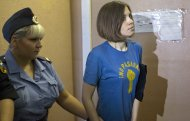 Feminist punk group Pussy Riot member Nadezhda Tolokonnikova is escorted at a court in Moscow, Russia, Wednesday, Aug. 8, 2012. Prosecutors on Tuesday called for three-year prison sentences for feminist punk rockers who gave an impromptu performance in Moscow's main cathedral to call for an end to Vladimir Putin's rule, in a case that has caused international outrage and split Russian society.(AP Photo/Misha Japaridze)