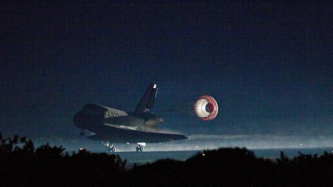 The drag chute is deployed as the space shuttle Atlantis lands at the Kennedy Space Center in Florida, completing STS-135, the final mission of the NASA shuttle program, on Thursday, July 21, 2011.  (AP Photo/ Houston Chronicle, Smiley N. Pool)