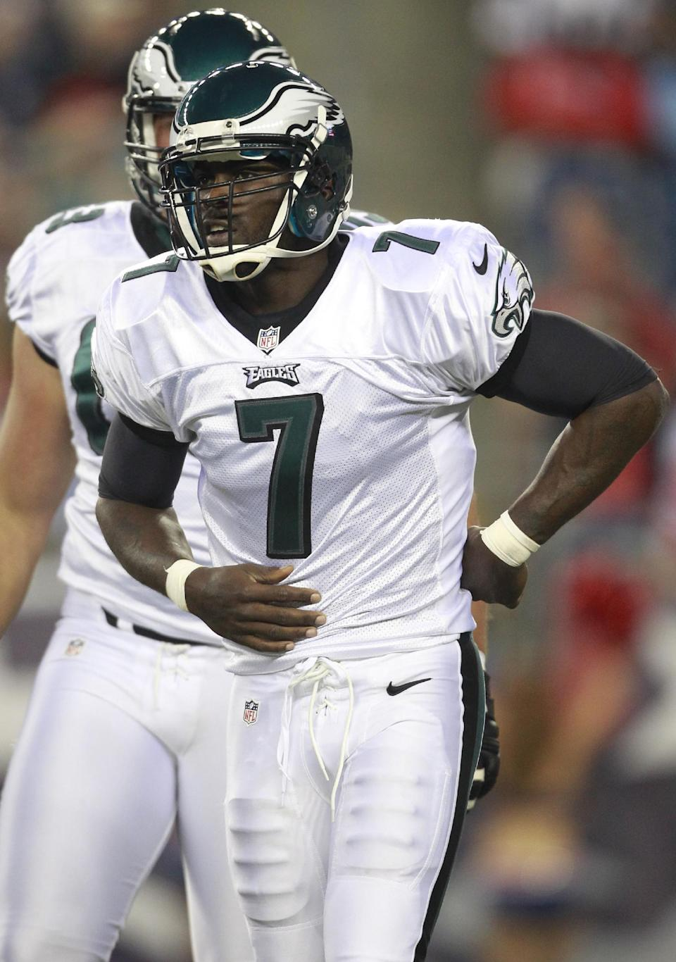 Philadelphia Eagles quarterback Michael Vick (7) holds his mid-section after getting hit hard by New England Patriots linebacker Jermaine Cunningham (96) during the first quarter of an NFL preseason football game in Foxborough, Mass., Monday, Aug. 20, 2012.  Vick left the game after the play. (AP Photo/Steven Senne)