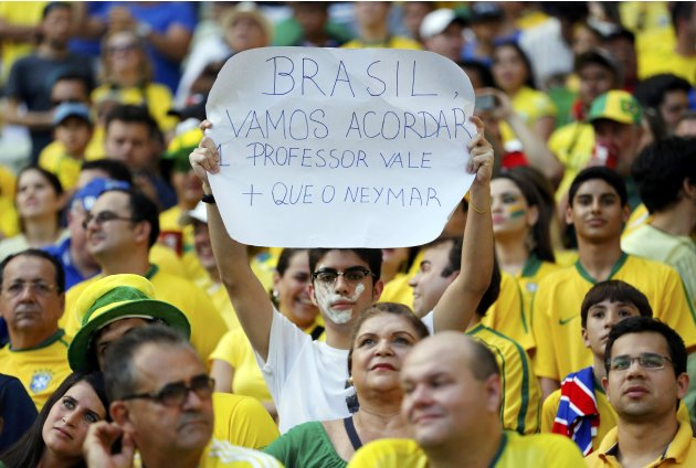 A protester holds up a sign before the Confederations Cup Group A soccer match between Brazil and Mexico at the Estadio Castelao in Fortaleza