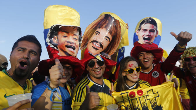 Soccer fans pose for a photo donning hats featuring cutouts of Colombian soccer stars, as they wait for the live broadcast of the World Cup quarterfinals' match between Brazil and Colombia, inside the FIFA Fan Fest area on Copacabana beach, in Rio de Janeiro, Brazil, Friday, July 4, 2014. (AP Photo/Silvia Izquierdo)