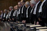 Court President Peter Tomka of Slovakia, fifth from right, and judge Hisashi Owada of Japan, fourth from right, take their seats with other judges at the World Court in The Hague, Netherlands, Monday Nov. 11, 2013. The United Nations' highest court was issuing its ruling Monday on a dispute between Cambodia and Thailand over land surrounding a 1,000-year-old temple near the Southeast Asian neighbors' border. (AP Photo/Peter Dejong)