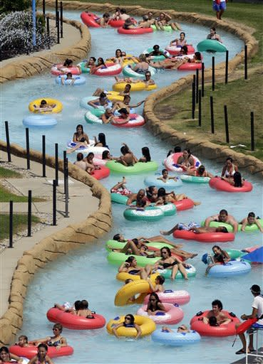 Swimmers try and keep cool in near 100 degree temperatures on a lazy river at Red Oaks Waterpark in Madison Heights, Mich., Thursday, June 28, 2012. (AP Photo/Paul Sancya)