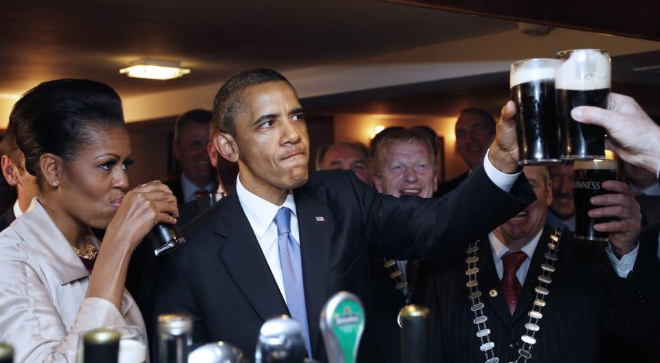 U.S. President Barack Obama and first lady Michelle Obama drink Guinness beer as they meet with local residents at Ollie Hayes pub in Moneygall, Ireland, the ancestral homeland of his great-great-great grandfather, Monday, May 23, 2011. (AP Photo/Charles Dharapak)