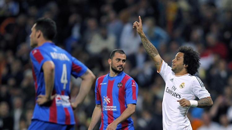 Real's Marcelo, right, celebrates his goal during a Spanish La Liga soccer match between Real Madrid and Levante at the Santiago Bernabeu stadium in Madrid, Spain, Sunday March 9, 2014. (AP Photo/Andres Kudacki)