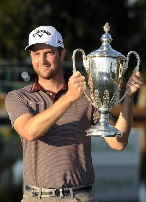Chris Kirk holds the trophy after winning the final round of the McGladrey Classic golf tournament on Sunday, Nov. 10, 2013, in St. Simons Island, Ga. (AP Photo/Stephen Morton)