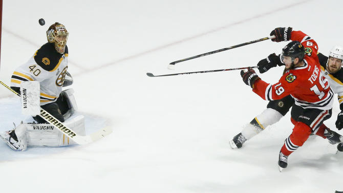 Chicago Blackhawks center Jonathan Toews (19) shoots the puck wide against Boston Bruins goalie Tuukka Rask (40) as Boston Bruins defenseman Andrew Ference (21) defends in the third period during Game 2 of the NHL hockey Stanley Cup Finals, Saturday, June 15, 2013, in Chicago. (AP Photo/Charles Rex Arbogast)