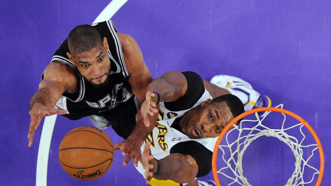 San Antonio Spurs forward Tim Duncan, left, shoots as Los Angeles Lakers center Dwight Howard defends during the first half of their NBA basketball game, Sunday, April 14, 2013, in Los Angeles. (AP Photo/Mark J. Terrill)