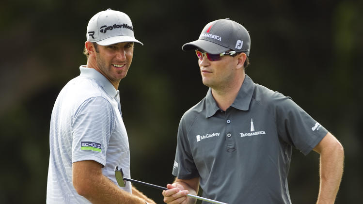 Dustin Johnson, left, stands with Zach Johnson on the first green during the first round of the Sony Open golf tournament on Thursday, Jan. 10, 2013, in Honolulu. (AP Photo/Marco Garcia)