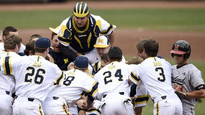 Maryland's Kevin Smith, right, walks off the field as Michigan celebrates a 4-3 win in the NCAA Big Ten tournament championship college baseball game Sunday, May 24, 2015, in Minneapolis. (AP Photo/Hannah Foslien)