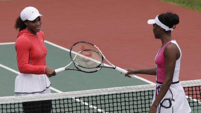 U.S. tennis players Serena Williams, left, and Venus Williams, right, greet each other before an exhibition tennis match in Lagos, Nigeria, Friday, Nov. 2, 2012. After months of injuries and illnesses, Venus Williams was all smiles as she interrupted a break during an exhibition match with her sister Serena to shake her hips to a Nigerian pop song. (AP Photo/Sunday Alamba)