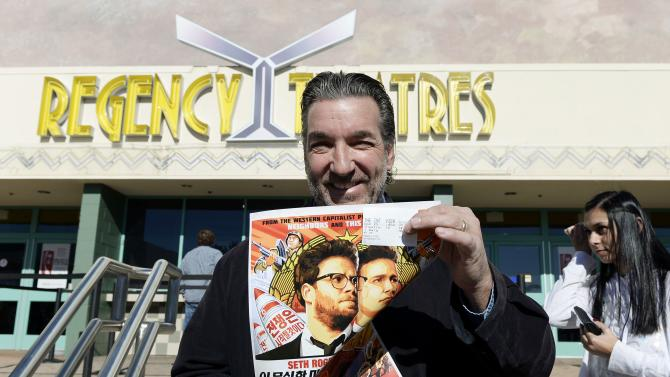 "Dennis Lavalle holds a ticket and a poster of the film ""The Interview"" as he attends the Christmas Day screening of ""The Interview"" in the Van Nuys section of Los Angeles"