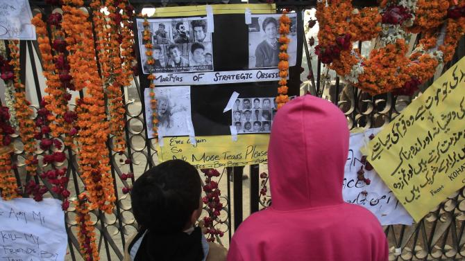 Children look at pictures of victims of Tuesday's attack on Army Public School in Peshawar