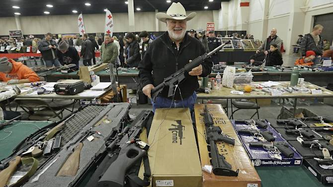 """FILE - In this Jan. 6, 2013 file photo, Ken Haiterman, of Pioneer Market, holds a CMMG 5.56mm AR 15 during the 2013 Rocky Mountain Gun Show in Sandy, Utah. A bipartisan quartet of senators, including two National Rifle Association members and two with """"F"""" ratings from the potent firearms lobby, are quietly trying to reach compromise on expanding the requirement for gun-sale background checks. (AP Photo/Rick Bowmer, File)"""