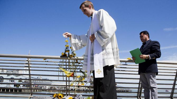 Father Cameron Faller of Restorative Justice Ministry drops holy water during a vigil for Kathryn Steinle, Monday, July 6, 2015, on Pier 14 in San Francisco. Steinle was gunned down while out for an evening stroll at Pier 14 with her father and a family friend on Wednesday, July 1. (AP Photo/Beck Diefenbach)