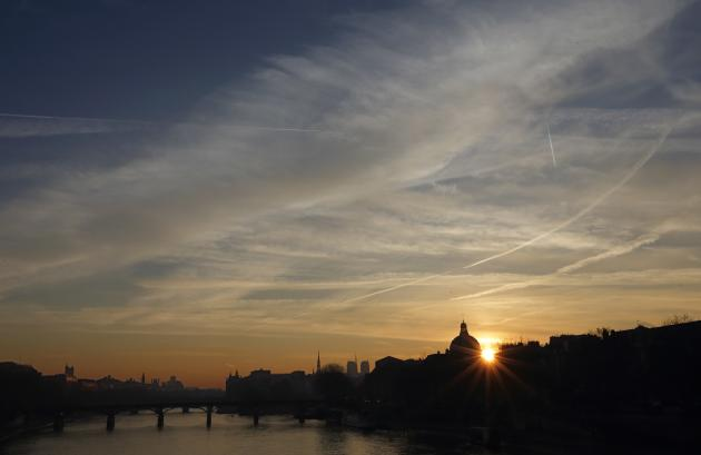 Clouds fill the sky as the sun rises on the Seine River in the early morning in Paris
