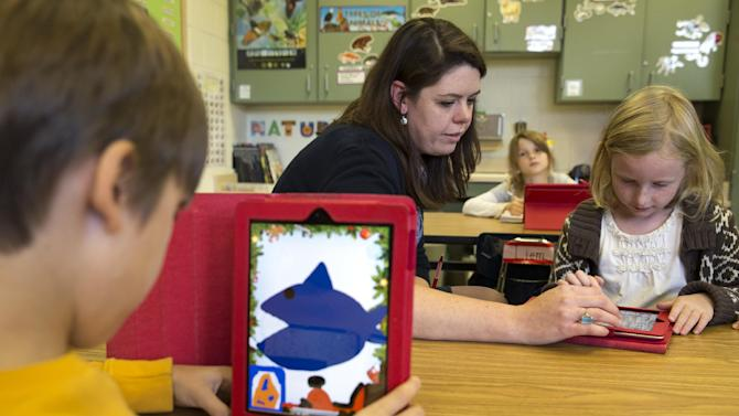 This photo taken Nov. 25, 2013 shows second grade teacher Heather Black working with Ingrid Soracco, 7, right, on her e-book assignment using an iPad at Jamestown Elementary School in Arlington, Va. Needed to keep a school building running these days: Water, electricity _ and broadband. Interactive digital learning on laptops and tablets is, in many cases, replacing traditional textbooks. Students are taking computer-based tests instead of fill-in-the bubble exams. Teachers are accessing far-off resources for lessons. (AP Photo/Jacquelyn Martin)
