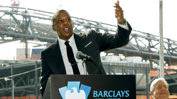 """FILE - In this Sept. 26, 2011 file photo, entertainer Shawn """"Jay-Z"""" Carter gestures during a news conference in front of Barclays Center, under construction in the background, as Brooklyn borough President Marty Markowitz, right, applauds in downtown Brooklyn, N.Y. Jay-Z, who is also the co-owner of the Brooklyn Nets, will open the team's new 18,000-seat arena with a concert series beginning on Friday, Sept. 28, 2012. (AP Photo/Kathy Willens, File)"""