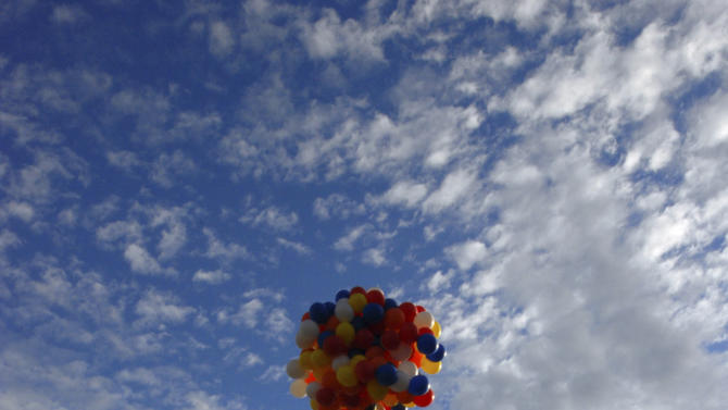 FILE- This July 5, 2008, file phot,o shows Kent Couch riding a lawn chair tied to more than 150 giant party balloons after taking off from his gas staition in Bend, Ore. Couch is planning to fly again July 14, this time in a tandem rig with Iraqi adventurer Fareed Lafta. The flight is a warm-up for a planned tandem flight this fall over Iraq. (AP Photo by Jeff Barnard, File)