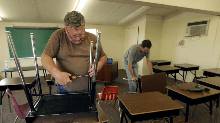 Volunteers Tommy Millender, left, and Brian Battershell, both from Temple, Texas arrange desks in a temporary classroom Sunday, April 21, 2013, four days after an explosion at a fertilizer plant in West, Texas. School will resume in for West students Monday in temporary facilities after Wednesday's explosion damaged three of the district's schools. The blast killed 14 people and injured more than 160 others. (AP Photo/Charlie Riedel)