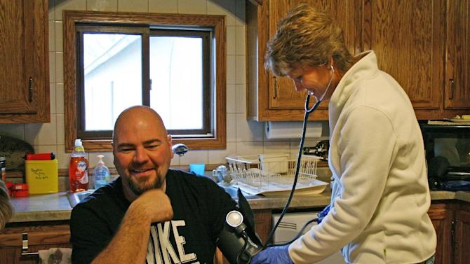 In this Dec. 2, 2013 photo, Nurse Dawn Dingeldein checks farmer Jay Vomastic's blood pressure in his home in Shawano County, Wis. Dingeldein works for the Rural Health Initiative, a program based in Shawano that sends nurses to farms to provide basic preventive care, including blood pressure, cholesterol and blood sugar checks. (AP Photo/M.L.Johnson)