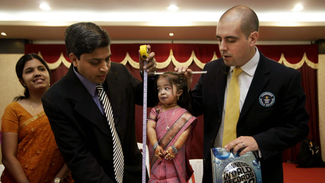 Guinness World Records adjudicator Rob Molloy, right, and Dr. Manoj Pahukar of Wockhardt hospital, second left, measure Jyoti Amge at a press conference in Nagpur, India, Friday, Dec. 16, 2011. Amge, 18, was declared shortest woman in the world measuring 62.8 centimeters (24.7 inches) by the Guinness World Records. (AP Photo/Manish Swarup)