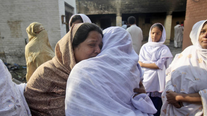 Pakistani Christian women comfort each other while standing outside a burned church in Mardan, Pakistan, Saturday, Sept. 22, 2012. In northwestern Pakistan, demonstrators burned the Sarhadi Lutheran Church on Friday, in the city of Mardan, but no one was injured, said senior police officer Salim Khan. (AP Photo/Mohammad Sajjad)