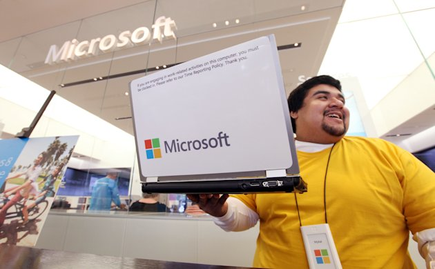 Microsoft store employee Mykal Carlton picks up his laptop sporting the new company logo, while also wearing a shirtt matching one of the four featured colors, and heads over to assist a customer Thur