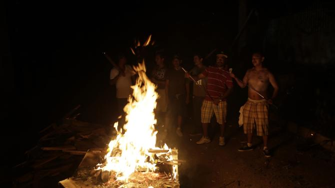 Residents prepared a bonfire as they stood outside at a street guarding their homes, as they face a lack of power, in Cabo San Lucas