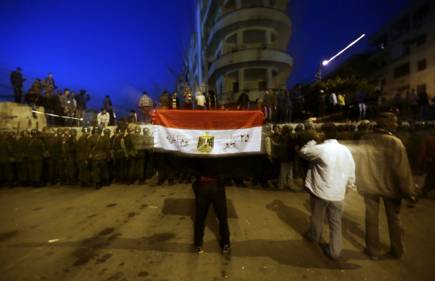 A protester holds the Egyptian national flag as army soldiers stand guard near the presidential palace in Cairo, Egypt, Sunday, Dec. 9, 2012. Egypt's liberal opposition called for more protests Sunday