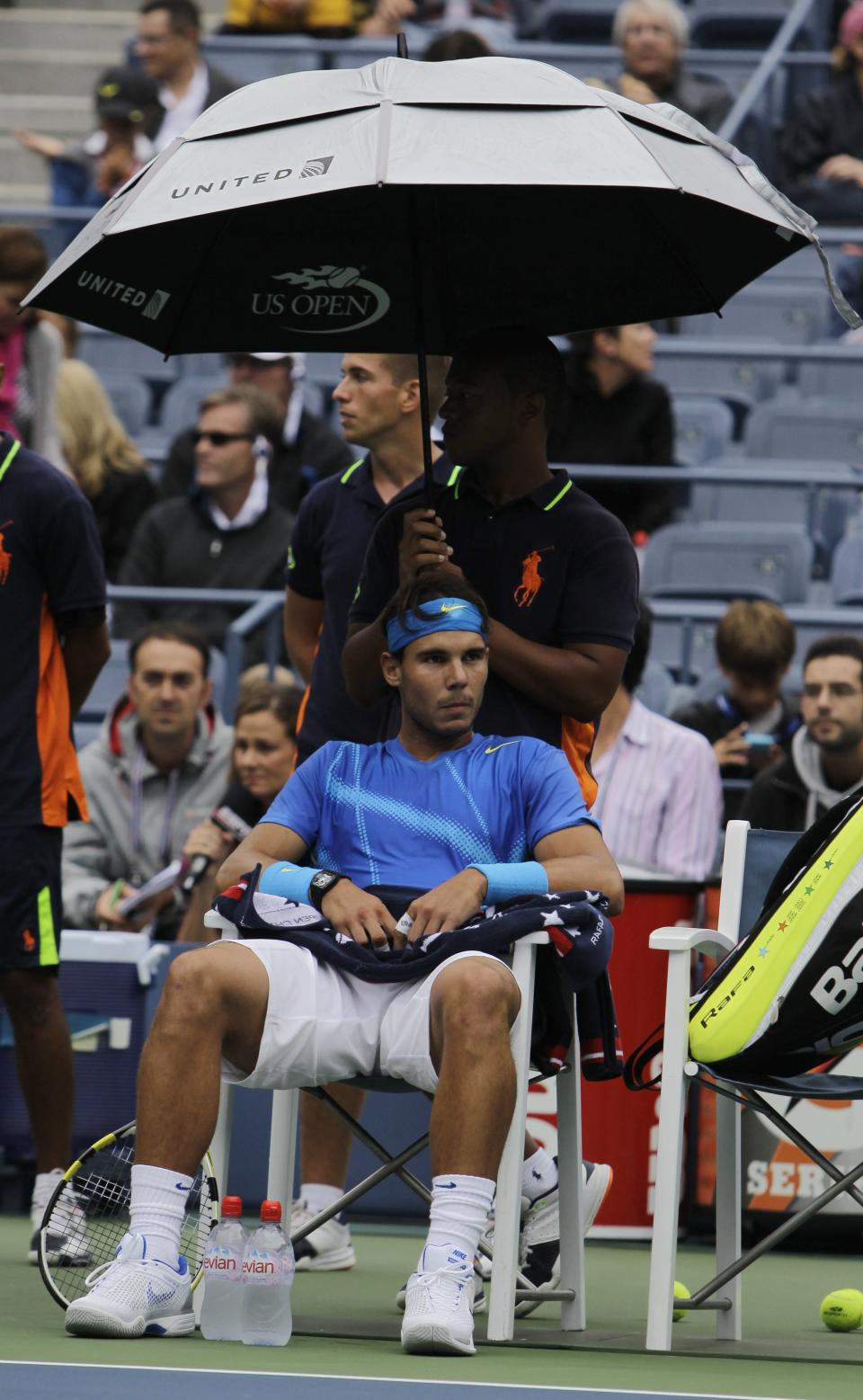 Rafael Nadal of Spain sits underneath an umbrella during his match against Gilles Muller of Luxembourg at the U.S. Open tennis tournament in New York, Wednesday, Sept. 7, 2011. Play was suspended due to rain. (AP Photo/Mike Groll)