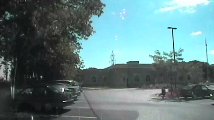 In this image taken from a Aug. 5, 2012 video from Oak Creek Police Lt. Brian Murphy's squad car camera, Wade Michael Page exchanges gunfire with Lt. Murphy, unseen, in the temple parking lot after Page emerged from the temple. The video shows Murphy rolling behind a parked car for cover and Page chasing him down, firing multiple shots at him. Milwaukee County District Attorney John Chisholm says Murphy was hit 15 times. Page killed himself following a firefight with Officer Sam Lenda. (AP Photo/Oak Creek Police Department)