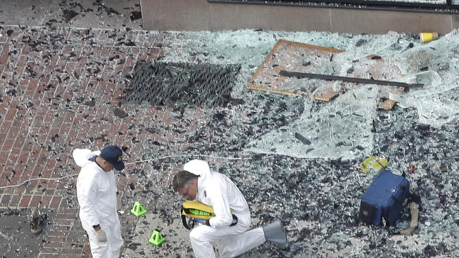 Two men in hazardous materials suits put numbers on the shattered glass and debris as they investigate the scene at the first bombing on Boylston Street in Boston Tuesday, April 16, 2013 near the finish line of the 2013 Boston Marathon, a day after two blasts killed three and injured over 170 people. The bombs that ripped through the Boston Marathon crowd were fashioned out of ordinary kitchen pressure cookers, packed with nails and other fiendishly lethal shrapnel, and hidden in duffel bags left on the ground, people close to the investigation said Tuesday. (AP Photo/Elise Amendola)