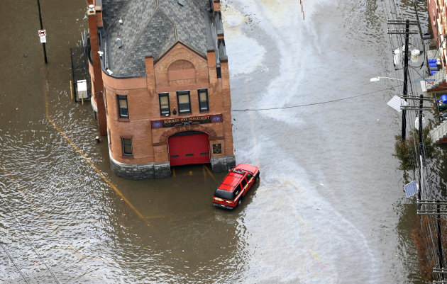 A firehouse is surrounded by floodwaters in the wake of superstorm Sandy on Tuesday, Oct. 30, 2012, in Hoboken, N.J. Sandy, the storm that made landfall Monday, caused multiple fatalities, halted mass transit and cut power to more than 6 million homes and businesses. (AP Photo/Mike Groll)
